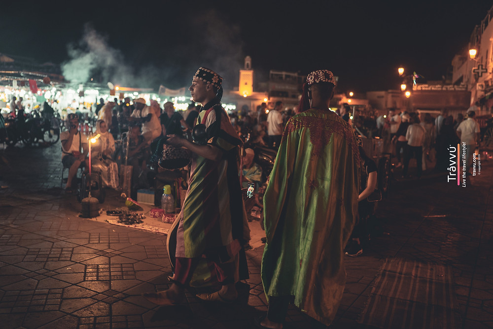 Local dancing at night whilst beating a drum. Steam from the markets and kitchens billow in the distance.