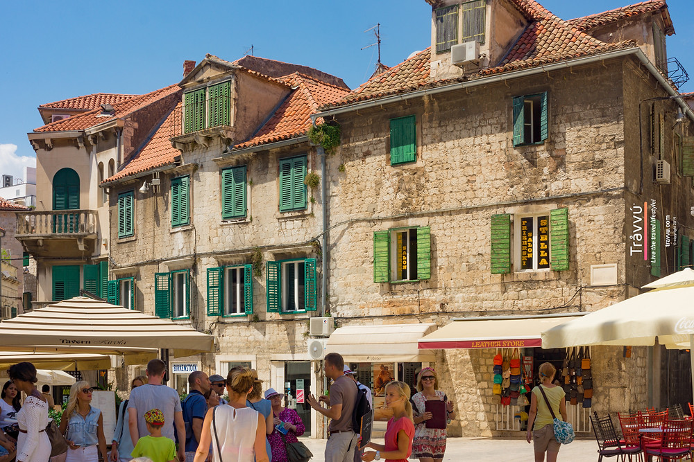 People in Split town centre choosing where to eat on a sunny day.