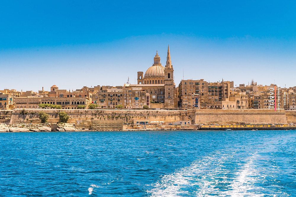 Valletta is seen on approach by the ferry boat from sliema. A yellow bricked city with a church dome in the centre.