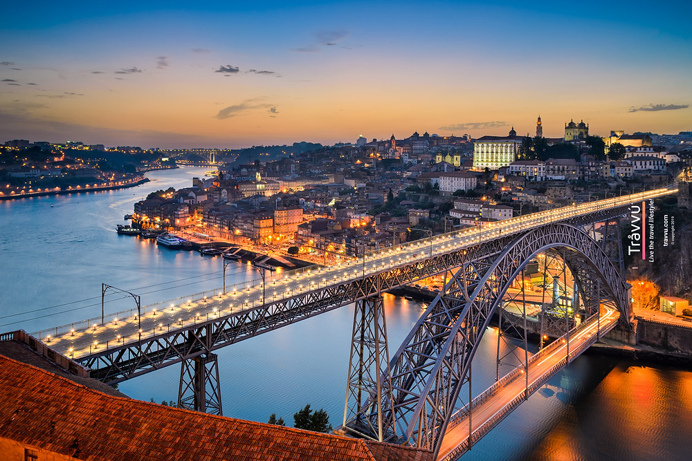 Night falls over the city of Oporto (Porto), lights from streets and building shimmer and reflect off the winding river that flows through the town.