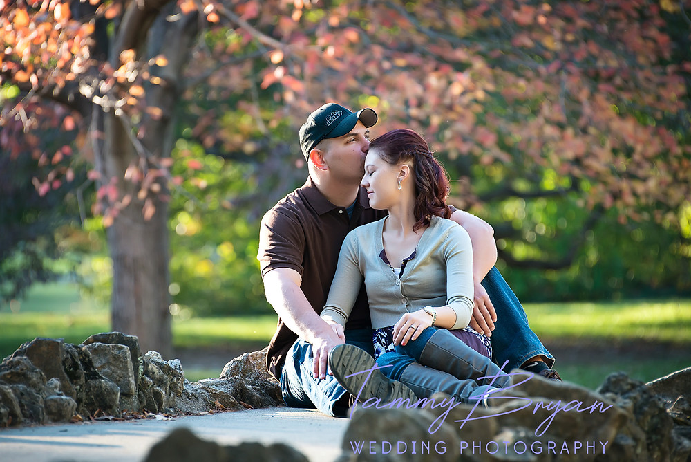 Engagement photography of a groom kissing his fiancé on her forehead sitting a rock bridge surrounded by trees by Cincinnati and Northern Kentucky best and most affordable wedding photographer Tammy Bryan