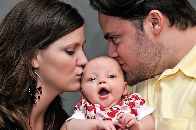 Cincinnati and Northern Kentucky best and most affordable wedding photographer Tammy Bryan's photobooth picture of a mother and father kissing a beautiful on the cheek