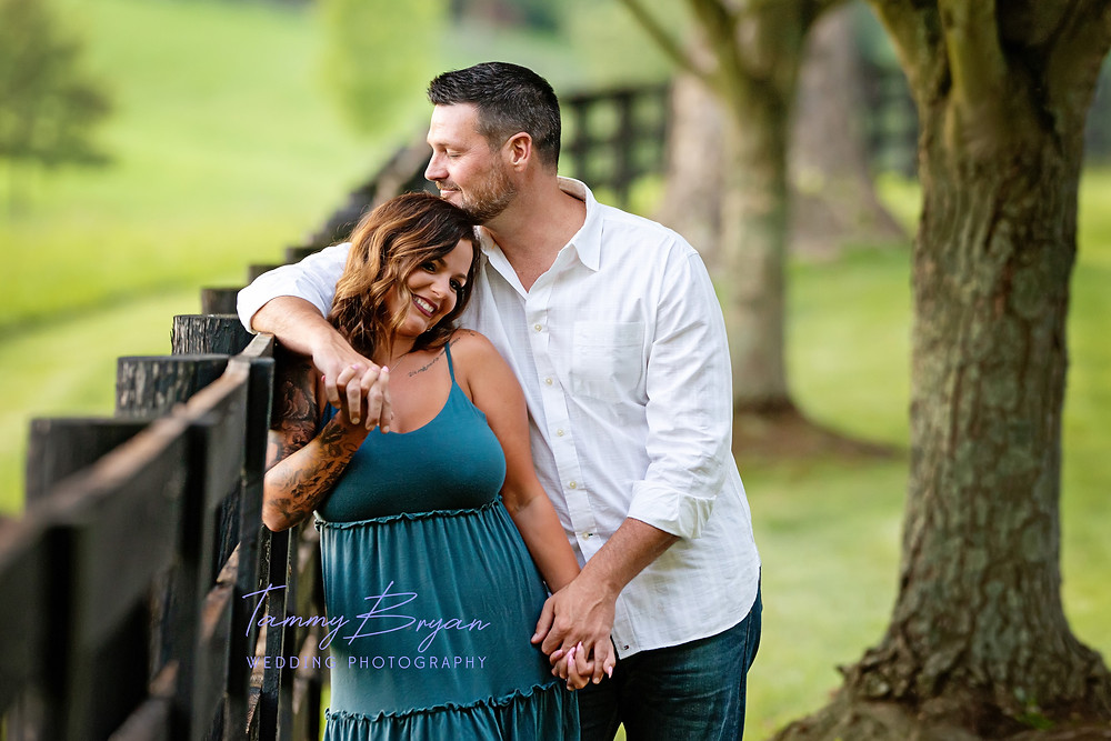 Engagement photography of a bride and groom by a wooden fence by Cincinnati and Northern Kentucky best and most affordable wedding photographer Tammy Bryan