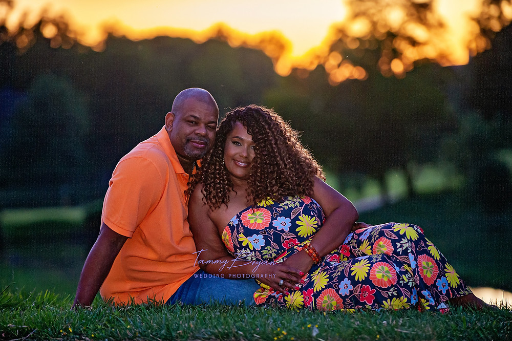 Engagement photography of a bride reclining in her fiancé's lap surrounded by trees by Cincinnati and Northern Kentucky best and most affordable wedding photographer Tammy Bryan