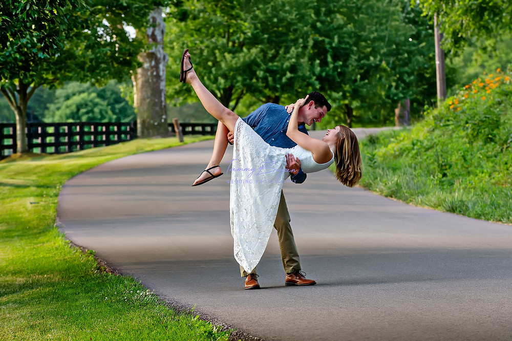 Engagement photography of a groom lifting his fiancé on a country road by a wooden fence by Cincinnati and Northern Kentucky best and most affordable wedding photographer Tammy Bryan