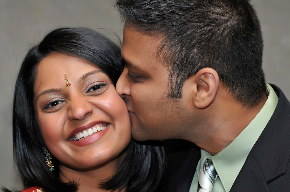 Cincinnati and Northern Kentucky best and most affordable wedding photographer Tammy Bryan's photobooth picture of a man kissing a beautiful Indian woman