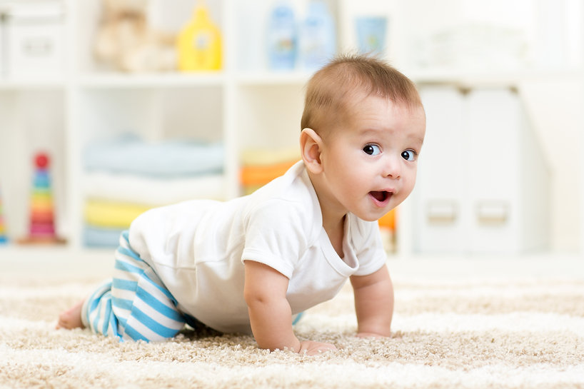 crawling funny baby boy indoors at home.