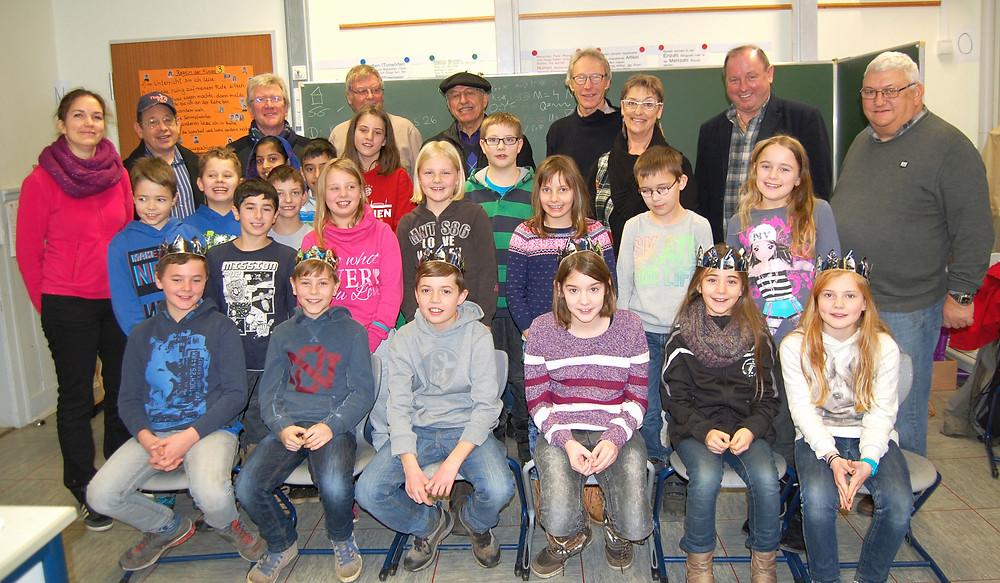 Die Viertklässler der Grundschule Wolf und ihre Lehrerin freuen sich über die Königskuchen und bedanken sich bei der Delegation aus Loudéac und vom Büdinger Verschwisterungsverein mit einem Lied.