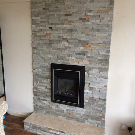 Stone tiled false chimney breast with tiled hearth