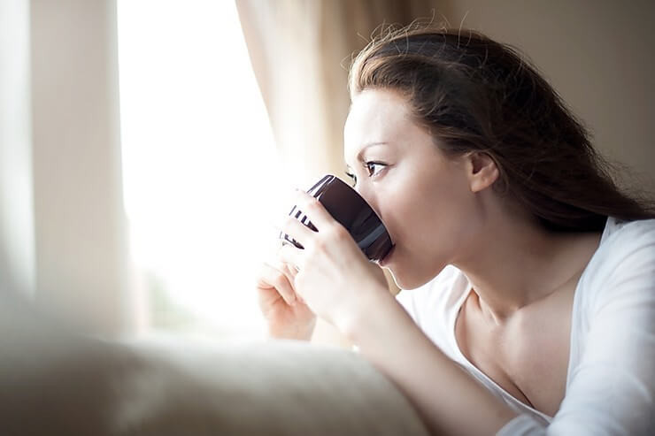 woman drinking coffee and looking out of the window