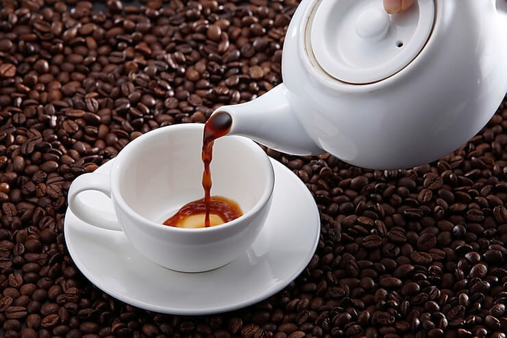Pouring coffee in a white cup with coffee bean background