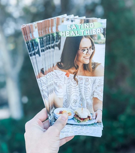 """hand holds several pamphlets with a woman on the front that read """"eating healthier"""""""