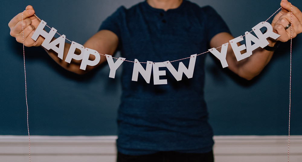 a man holds a string of happy new year letters