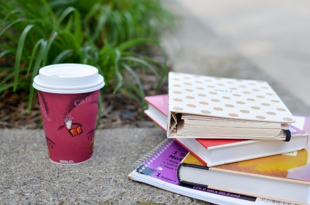 A to-go coffee mug and a stack of books outside.