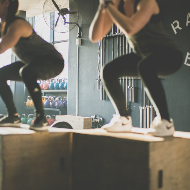 Two females doing box jumps