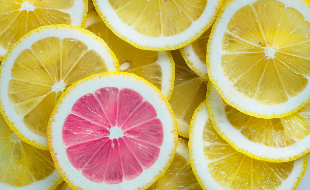 One pink lemon slice on a pile of yellow lemon slices