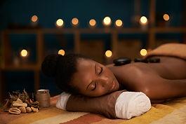 Young woman enjoying stone massage in lu