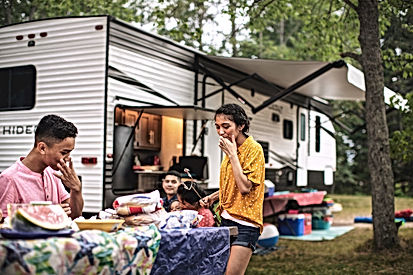 family at campsite with keystone hideout travel trailer