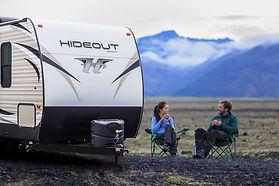 Couple sitting outside Keystone Hideout Travel Trailer RV