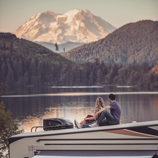 Couple sitting outside camper ovelooking mountains and lake