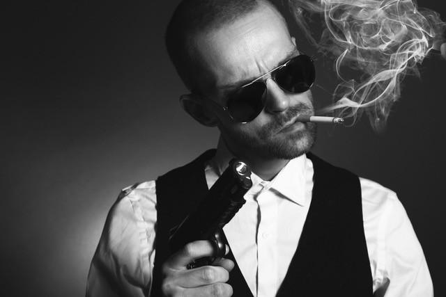 Villain with gun, cigarette, and dark glasses