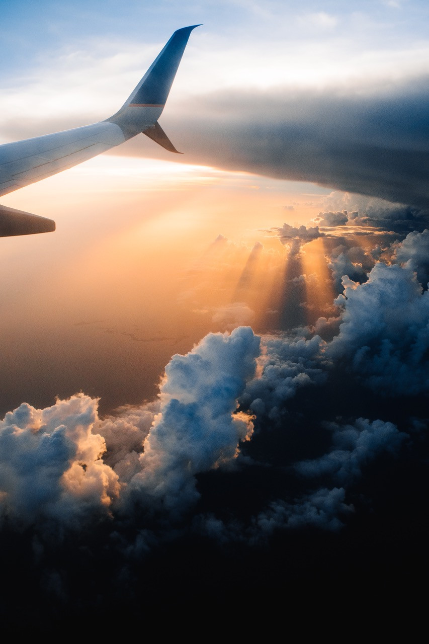 Plane flying in sunset clouds
