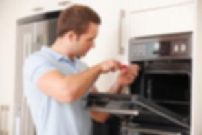 Man Repairing Domestic Oven In Kitchen.jpg