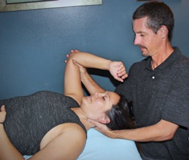 Brian Phillips, LMT provides a myofascial release treatment to improve range of motion in client's neck and shoulder.