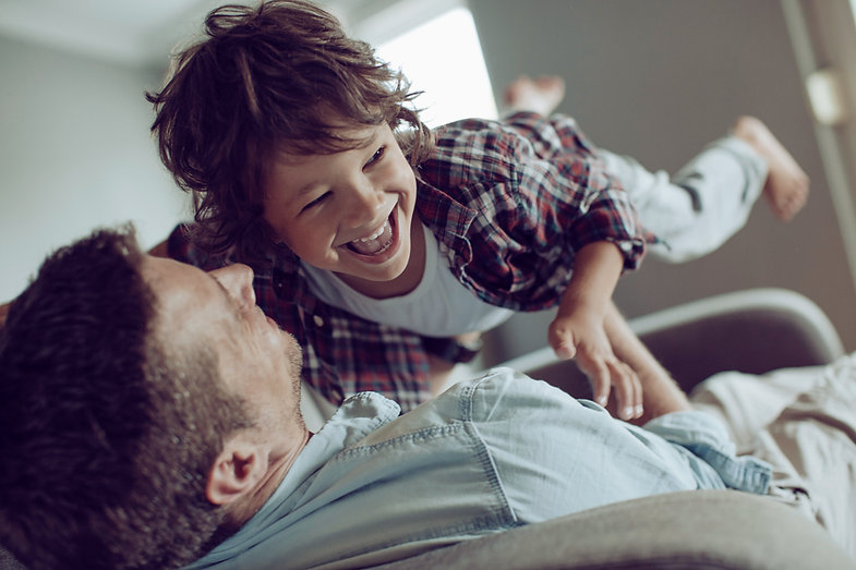 A father and son play happily, protected by Stewart's United Agencies Insurance
