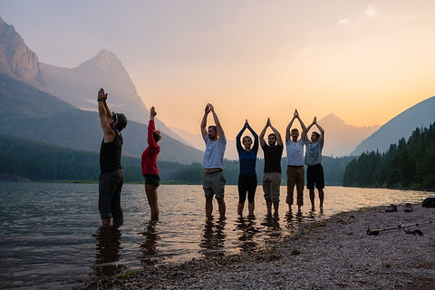 A group of men and women with their hands above their heads in prayer, ankle deep in a lake overlooping rolling hills and mountain peaks at sunset.