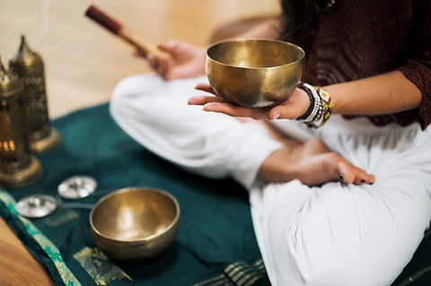 Brown skinned woman in baggy white pants sitting crosslegged on a blue mat holding a tibetan singing bowl and a mallet. There is another singing bowl and finger cymbals on the ground in front of her.