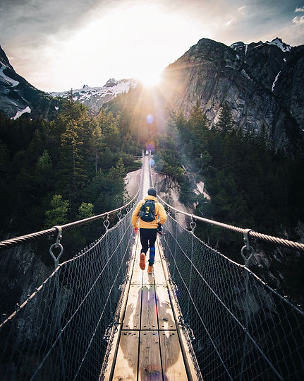 Young man in hiking gear, a backpack and hat facing away from the image walking over a thin, wooden suspension bridge over a valley in the woods.