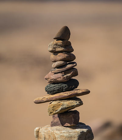 A series of brown, tan, black and rose colored stones of different shapes and sizes balanced on top of one another forming a tower.