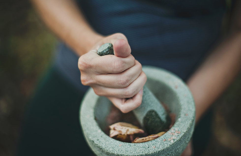 a white women's hand grinding up herbs with a stone mortar and pestle.