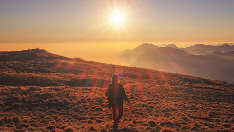 A woman in a barren valley facing away from the camering looking at the misty mountains in the distance with beams of sunlight radiating down.