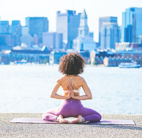 Woman in a string sports bra in reverse prayer yoga pose looking away from the camera towards a river and city landscape.
