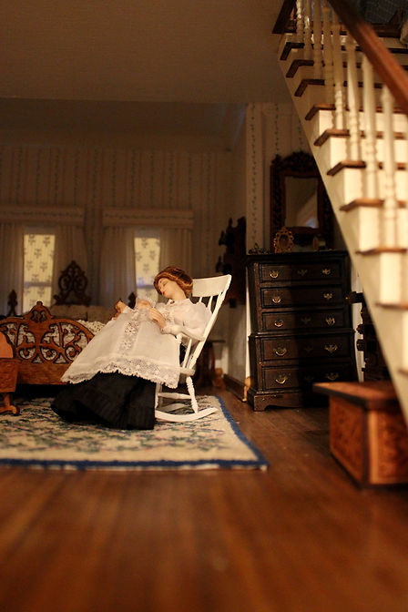 A view of a miniature woman rocking a miniature baby next to a staircase in a dollhouse