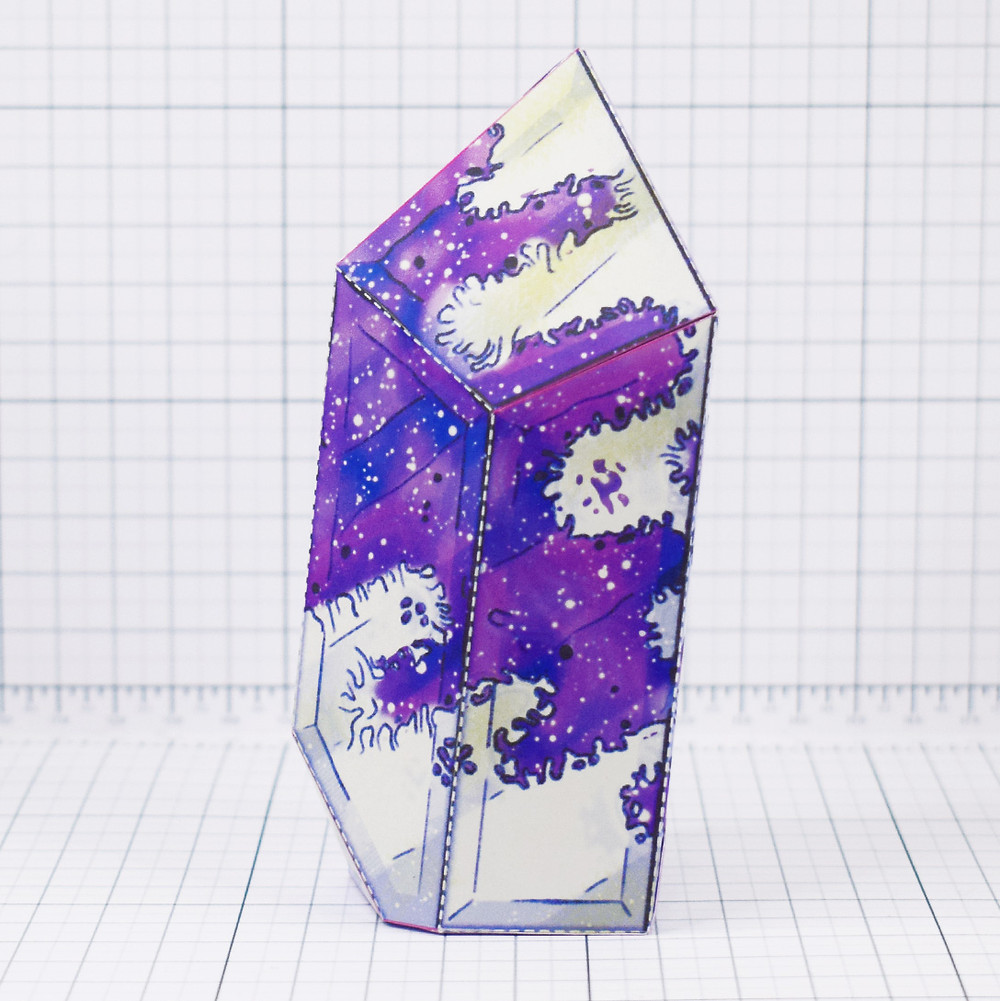 A papercraft crystal covered in a purple galaxy like mold.