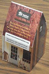 cardboard coin bank of a Habitat house