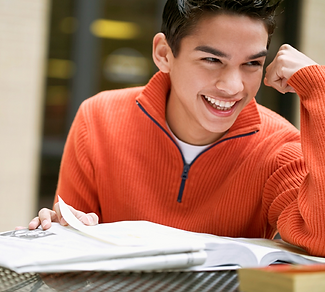 Smiling student sitting with his school work and textbook