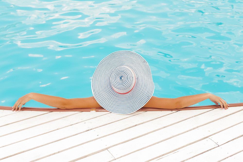 Girl with a striped hat laying in the pool sunbathing