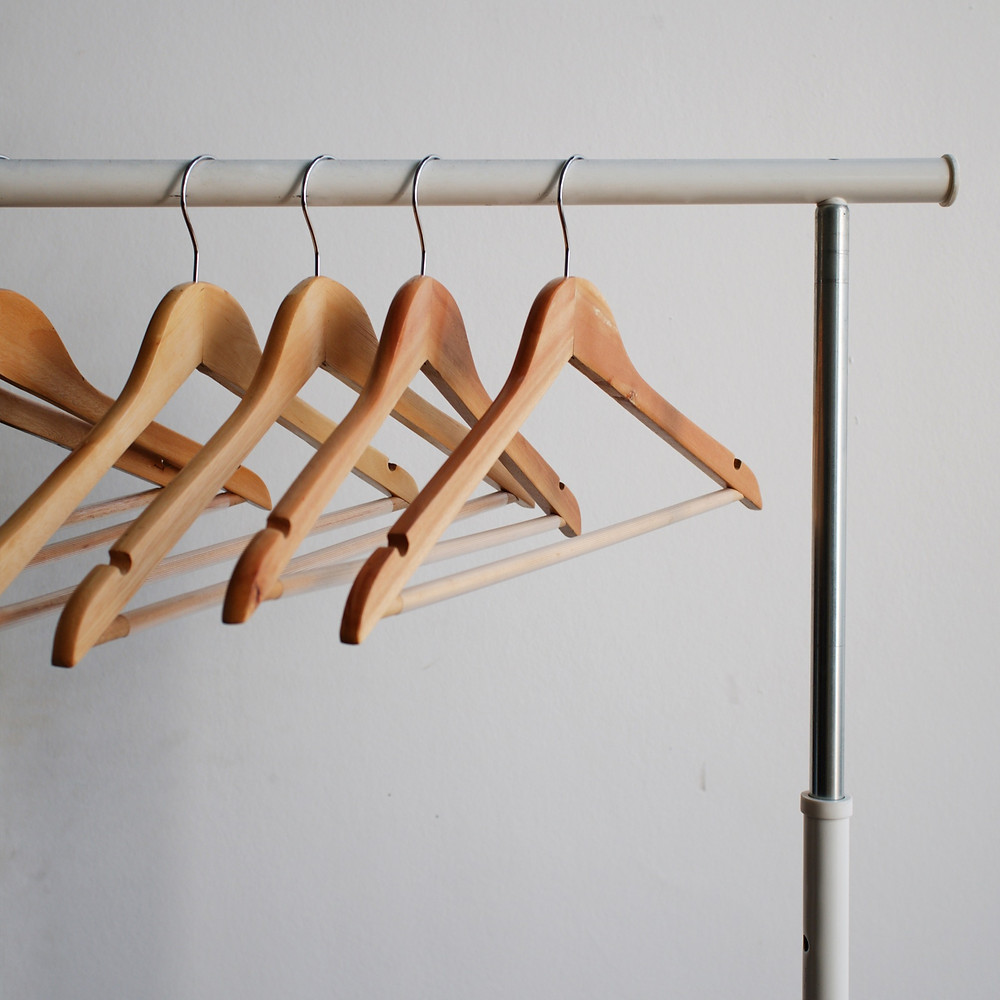 Wooden hangers with no clothes against a white background