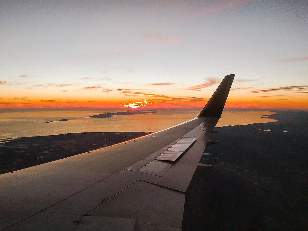Sunset view from an airplane window over the ocean
