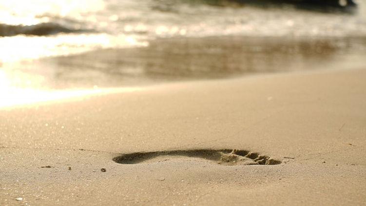 huellas-playa-arena-ola-creciente_17887-