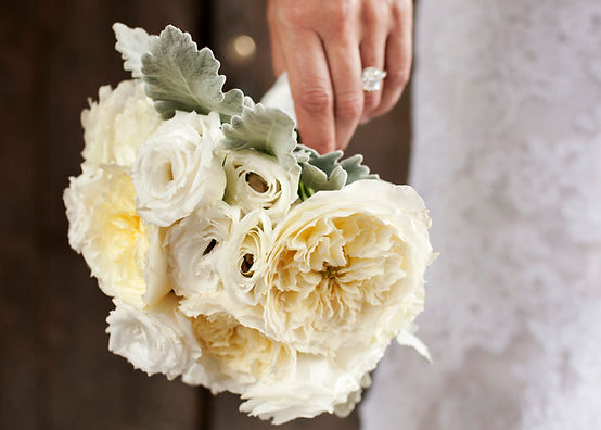 Bridal bouquet of white flowers by Matthew Robins Design for a wedding planned by wedding planner Imagine Party and Events. The diamond engagement ring was a 6 carat cushion cut ring and the wedding ceremony and wedding reception was held at Blue Hill Stone Barnes.