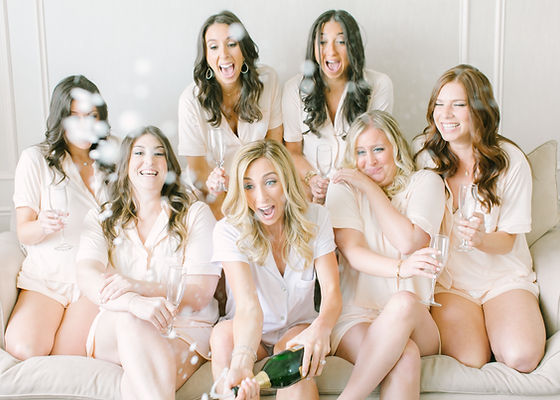 Beautiful bridesmaids getting ready with champagne in blush pink matching pajamas.  Luxury wedding in Westchester, New York.  Wedding planned by wedding planner Imagine Party and Events.
