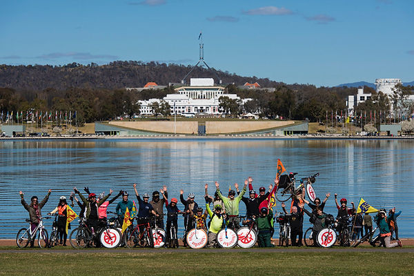 CBR - cyclists arms up with parliament -