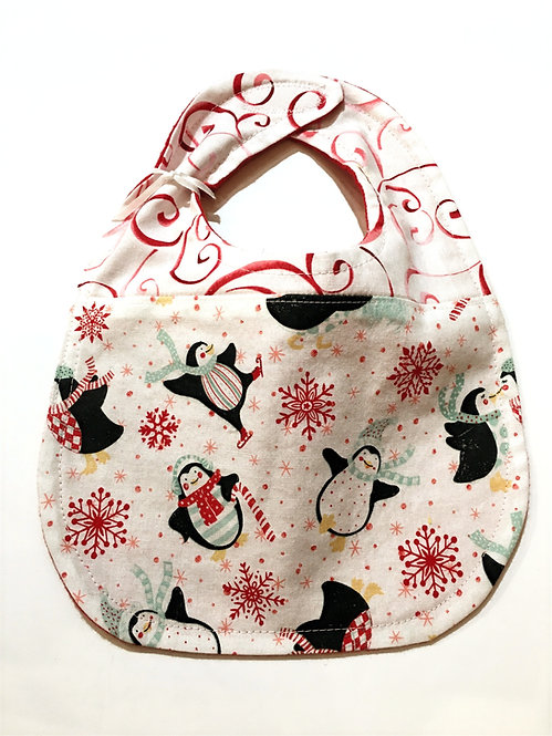 red & white oval-shaped cloth baby bib with penguins on skates in red, white & black