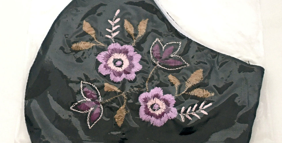 Side view of folded navy cotton mask with embroidery of 2 purple, lilac & white flowers & purple buds, taupe leaves
