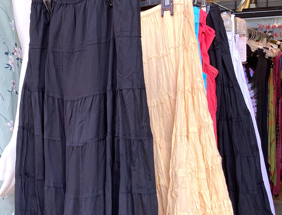 Rack with long black and sand colored skirts hanging on it